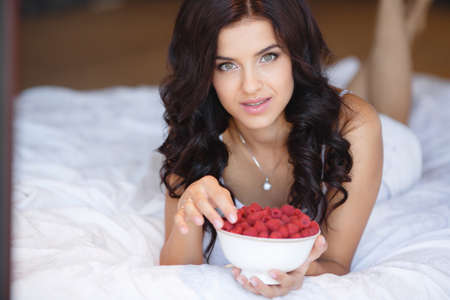 woman eating fruit: woman laying on the floor with bowl of berries blueberries at home. fresh morning. healthcare. Portrait of beautiful young woman eating a bowl of blueberries and smiling. Healthy food. Stock Photo