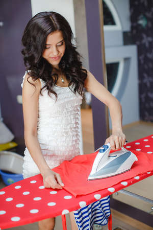 the iron lady: Happy young beautiful woman ironing clothes. Housework. woman ironing clothes on the table. Smiling young woman ironing clothes at home. Young beautiful woman ironing clothes in room