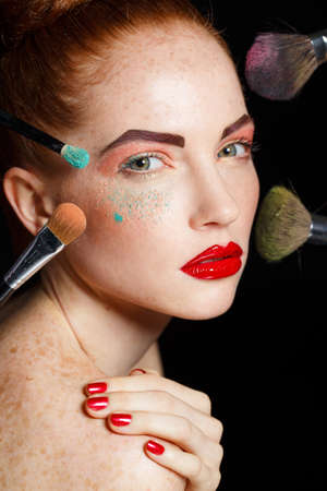 black makeup: make up woman with makeup brushes. Beautiful Face. Makeover. Perfect Skin. Applying Makeup. Make-up girl, woman teenager face with make up brushes and a blusher. Woman posing on black background Stock Photo