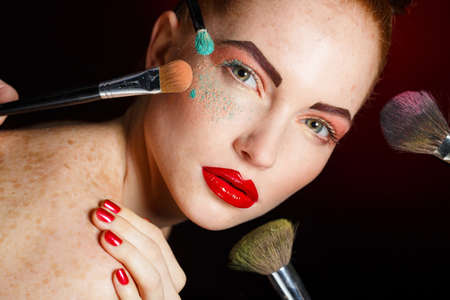 make up woman with makeup brushes. Beautiful Face. Makeover. Perfect Skin. Applying Makeup. Make-up girl, woman teenager face with make up brushes and a blusher. Woman posing on black background Standard-Bild
