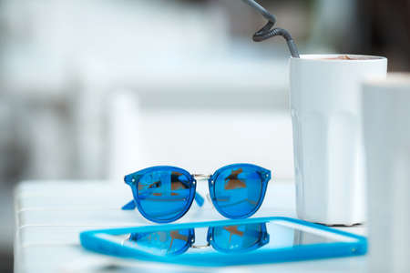 web surfing: Digital tablet computer with cup of coffee on old wooden table in white cafe. Simple workspace or coffee break with web surfing. bue sunglasses Stock Photo