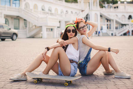 fun day: Two beautiful girlfriends, young athletic girl brunette in sports shoes and shorts, glasses, ride on a skateboard in the city, sunny, leisure, portrait of a smiling woman outdoors, healthy lifestyle, extreme sports.