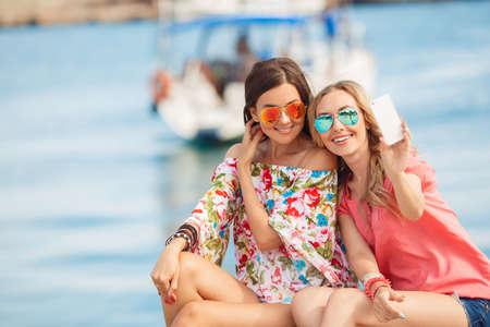 """Schöne Mädchen mit Einkaufstüten, die ein """"selfie"""" mit ihrem Handy. Ausverkauf, Konsum, Technologie und Menschen Konzept glückliche junge Frauen mit Smartphones und Einkaufstaschen, die Selbstportrait. Standard-Bild - 45892637"""