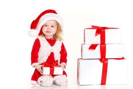 bebes niñas: Niño feliz, niña linda con el pelo rizado rubio y ojos marrones, con una dulce sonrisa, vestido como Santa Claus con una gran tapa de color rojo en la cabeza, al lado de cajas de regalo, retrato de estudio sobre fondo blanco