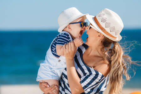 sandy beach: The happy family relaxing near the sea young mother with the little son, are dressed in striped t-shirts and white shorts, sun glasses, have fun together on a sandy beach on a wooden path against the clear blue sky and the blue sea.