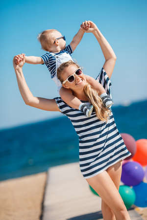 clear path: The happy family relaxing near the sea young mother with the little son, are dressed in striped t-shirts and white shorts, sun glasses, have fun together on a sandy beach on a wooden path against the clear blue sky and the blue sea.