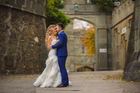 Ślub: Bride oraz oczyszczenie ich? Lubu spacer na świeżym powietrzu w parku, wiosna para nowożeńców, szczęśliwa kobieta i mężczyzna w dzień ślubu przytulanie w zielonym parku, kochający para w strojach ślubnych patrząc na siebie, panna młoda i pan młody blond - czarny