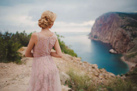 decollete: The beautiful woman, the blonde with brown eyes, in a wedding dress of pink color, in ears are dressed earrings with pearls, poses sitting on the high rocky coast with a beautiful view of the blue sea, a summer portrait of the happy bride