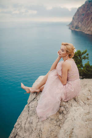 sea scenery: The beautiful woman, the blonde with brown eyes, in a wedding dress of pink color, in ears are dressed earrings with pearls, poses sitting on the high rocky coast with a beautiful view of the blue sea, a summer portrait of the happy bride