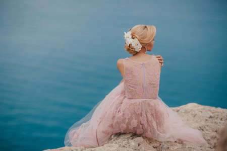 sea cliff: The beautiful woman, the blonde with brown eyes, in a wedding dress of pink color, in ears are dressed earrings with pearls, poses sitting on the high rocky coast with a beautiful view of the blue sea, a summer portrait of the happy bride