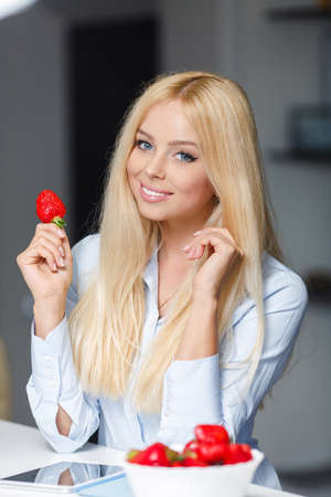 strawberry: Beautiful young woman with plate of strawberries in kitchen. Smiling woman eating strawberry. Close up female face portrait. Healthy mel on a plate.
