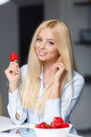 fresa: Joven y bella mujer con plato de fresas en la cocina. Sonriente mujer de comer fresas. Ciérrese encima de cara femenina retrato. Mel saludable en un plato.