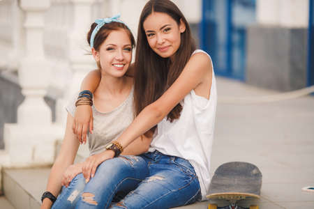 modern girls: Lifestyle, two beautiful young women, beautiful girlfriends, brunette, dressed in a light sleeveless shirts and blue jeans, spend time together on city streets in the summer, having fun and smiling Stock Photo