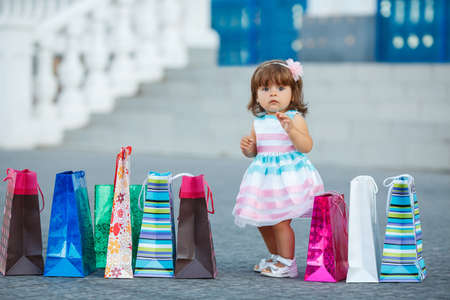 differential focus: A small child, a girl, a brunette with curly hair and brown eyes, in a light summer dress, one is near a shopping Mall with colorful bags, cute baby goes shopping with bags, shopping little girl in the big city. Stock Photo