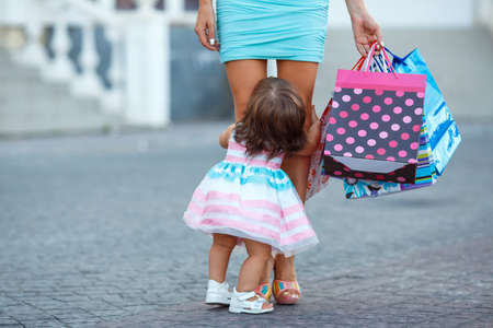 mum and child: Happy family, Mother and her little daughter, go shopping with colored bags together when shopping, family shopping in a big city, a young woman during the shopping with a little girl, consumerism and people concept Stock Photo