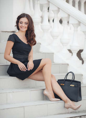 educational institution: A beautiful young woman of Asian appearance, with long brunette curly hair, in a black short dress without sleeves, a student of the prestigious educational institution, sits on the steps near the white railing, summer, Sunny day