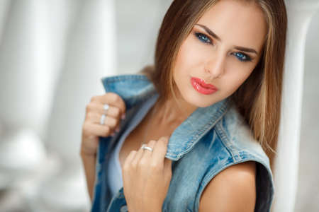 straight jacket: Summer portrait of a beautiful woman, Happy young woman with long straight hair, brunette with blue eyes, beautiful makeup, dressed in a blue denim jacket without sleeves, poses for a photograph in the open air in the summer.