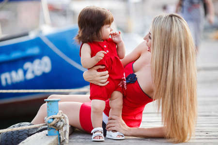 wearing sandals: The mother, a woman with beautiful legs in white sandals, walks on the boardwalk with her small daughter, girl, brunette with brown eyes, wearing a red dress and white sandals, mother and daughter holding hands each other