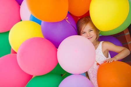 風船で遊ぶ少女。空気風船で遊ぶ少女の肖像画。カラフルな風船を持って幸せな女の子。笑顔の子供。幸福