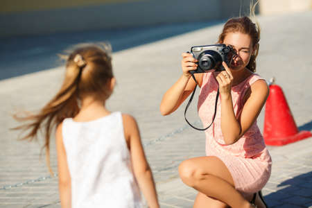 happy family nature: Mother making photos of her daughter child. Mother photograph child outdoor. Mother with camera. Child posing to the camera. Mother photographing her daughter