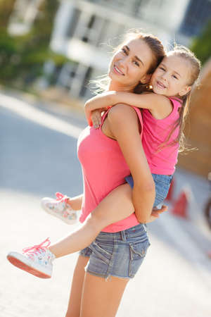 Beautiful and happy young mother giving piggyback ride to her daughter. Both smiling and looking into the camera. Summer city in background. Mother holding daughter outdoors smiling