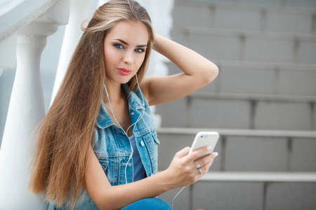gray eyes: A lovely young woman, brunette with long straight hair and gray eyes, dressed in a dark blue denim jacket without sleeves, sitting on the stairs in a subway, wearing headphones, listening to your favorite music from your mobile phone