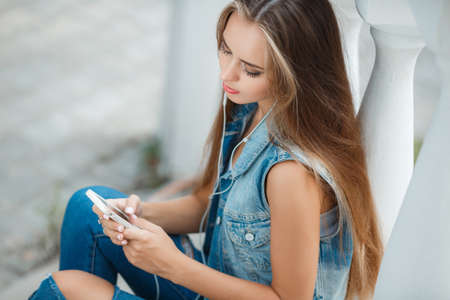 straight jacket: A lovely young woman, brunette with long straight hair and gray eyes, dressed in a dark blue denim jacket without sleeves, sitting on the stairs in a subway, wearing headphones, listening to your favorite music from your mobile phone