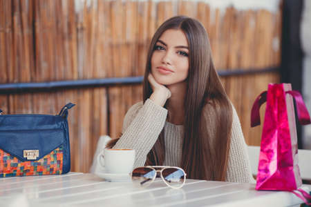 長いストレートの髪と茶色の目、色の袋で疲れるショッピングの後で若い美しいブルネットの女性は、ホット コーヒーのカップと夏のカフェのテー