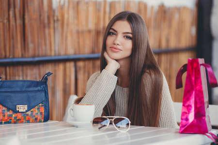 Jonge mooie brunette vrouw met lang sluik haar en bruine ogen, na een vermoeiende winkelen met gekleurde zakken, besteedt zijn tijd zitten aan een tafel in een zomer cafe met een kop warme koffie.