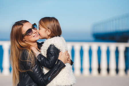 Happy family, mother and daughter, brunette, long straight hair, dressed in black leather jackets, spend time together, cuddling and walking along the promenade in the resort town near the sea, clear, Sunny spring day.