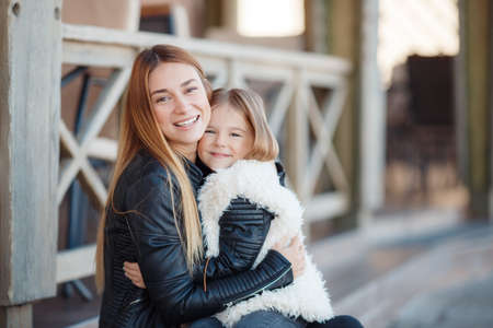 stylish: Portrait of happy family, mother and daughter, daughter brunette and redhead mom, long straight hair, dressed in black leather jackets, spend time together, sitting together on the steps outside the house, Sunny spring day, joy and family happiness Stock Photo