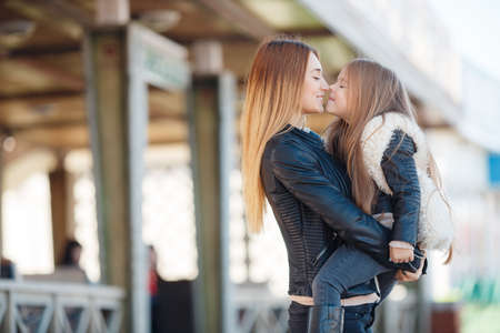 Spring portrait of a happy family, red-haired mother and daughter brunette with long straight hair, dressed in black leather jackets, spend time together, mother holds daughter on hands standing near a country house.