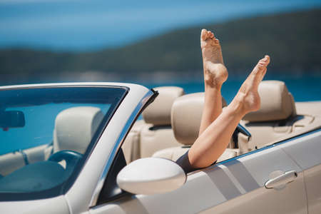 shapely legs: Shapely barefoot female legs peeking out of a beautiful white convertible, standing on a background of mountains and blue sky outdoors in the summer.