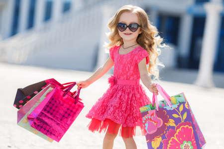 Ein schönes kleines Mädchen im Vorschulalter, eine Brünette mit dem lockigen Haar, rosa Sommerkleid, bunten Papier-Taschen, Sonnenbrillen, mit einem süßen Lächeln, man geht einkaufen zur Mall, Helfer der Mammas in der Großstadt, Shopping