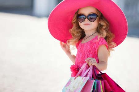 Modieuze meisje van voorschoolse leeftijd in grote roze hoed, brunette, krullend haar, roze zomerjurkje, kleurrijke papieren zakken, de zonnebril gaat men om te winkelen bij het winkelcentrum, winkelen, helper mama's in de grote stad