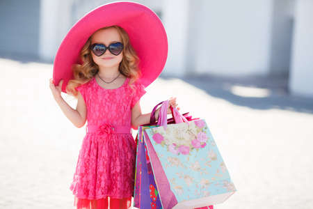 children clothing: Fashionable little girl of preschool age in large pink hat, brunette, curly hair, pink summer dress, colorful paper bags, the sunglasses one goes for shopping to the Mall, shopping, moms helper in the big city