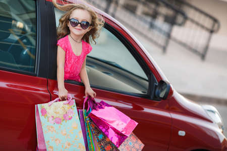 eye wear: Joyful little girl of preschool age, a brunette with curly hair in a pink summer dress, looking out the window of the red car, in the hands holding colorful paper bags, eye wear sunglasses, came to a shopping center, shopping