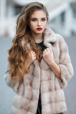 Autumn photo shoot in the city for a beautiful woman.Portrait of beautiful young woman, model with long blond curly hair and gray eyes, light makeup and red lipstick, dressed in fur jacket beige, autumn photo shoot on a background of city streets
