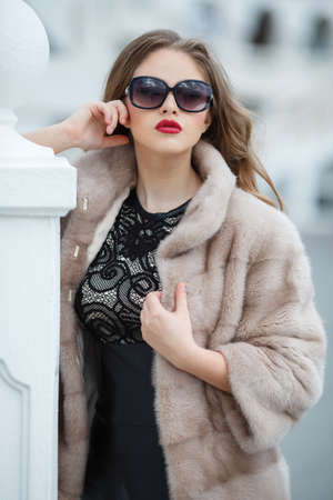 gray eyes: Portrait of beautiful young woman model with long blond curly hair and gray eyes, light makeup and red lipstick, dressed in fur jacket beige, sun glasses, autumn photo shoot on the background of city streets