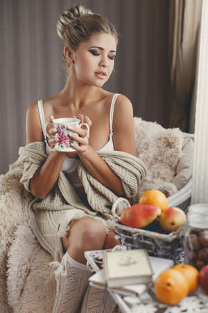 Young woman at home sitting on modern chair in front of window relaxing in her living room reading book and drinking coffee or tea. Autumn. Home. Cozy.Soft cozy photo of woman cup of tea in hands