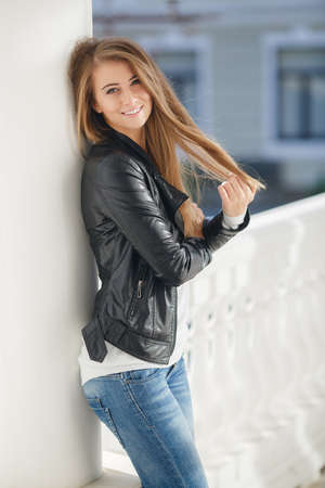 black sweater: Happy young woman brunette with long straight hair and gray eyes, spends time outdoors in the city, dressed in a white sweater, blue jeans and black leather jacket, a beautiful smile, posing for the photographer on the street in the afternoon