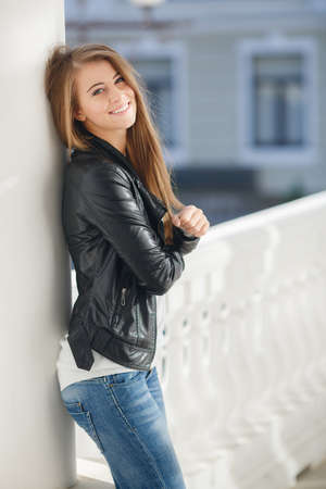 Happy young woman brunette with long straight hair and gray eyes, spends time outdoors in the city, dressed in a white sweater, blue jeans and black leather jacket, a beautiful smile, posing for the photographer on the street in the afternoon
