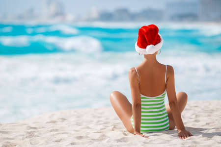 sexy santa girl: Woman on the beach in santas hat.Beautiful snow maiden in red cap of Santa Claus and a green striped swimsuit, spends the Christmas holidays sitting on tropical white sand beach near blue ocean Stock Photo