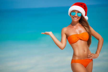 Maiden in orange bikini and hat of Santa Claus.A young girl with a beautiful figure, in an orange bikini, blue sun glasses and a red cap of Santa Claus spends Christmas vacation on a tropical beach