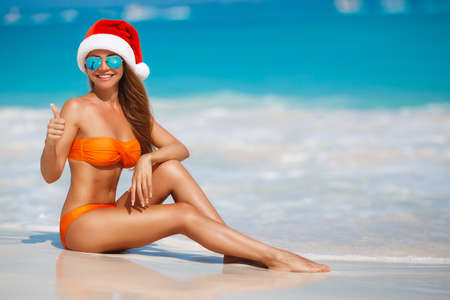 female christmas: Woman on the beach in Santas hat.Beautiful snow maiden in red cap of Santa Claus and orange bikini, holds new years eve, sitting on a tropical white sand beach near blue ocean
