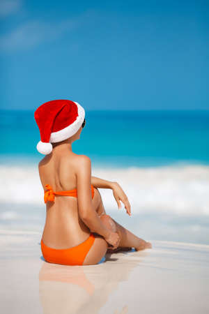 santa hat: Woman on the beach in Santas hat.Beautiful snow maiden in red cap of Santa Claus and orange bikini, holds new years eve, sitting on a tropical white sand beach near blue ocean
