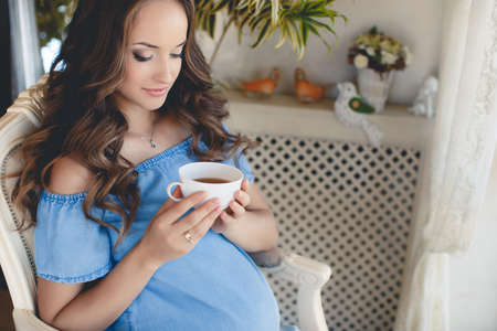 A young pregnant woman with a cup of tea.Beautiful young pregnant woman, brunette with long curly hair and light makeup, sitting on the floor at home with a cup of hot tea in his hands Standard-Bild