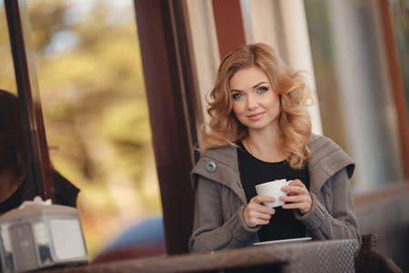 gray eyes: Young beautiful woman the blonde with gray eyes and long curly hair, sitting alone at a table in an outdoor caf in spring city, enjoy strong coffee from a white Cup, is dressed in a knitted sweater with long sleeves