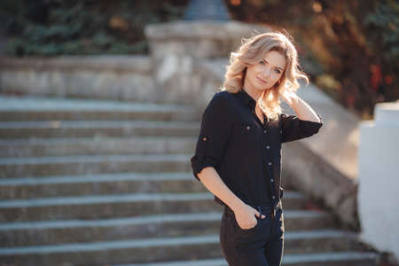 gray eyes: An attractive young woman, blonde with curly hair and gray eyes, dressed in a black shirt and black pants, posing in summer night in the city Park on the steps Stock Photo