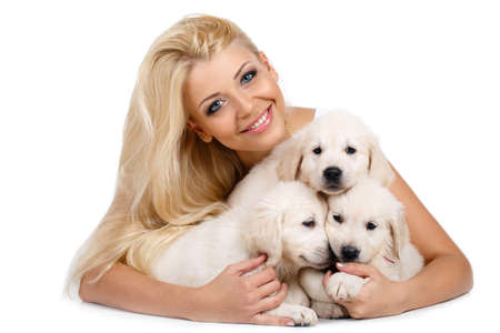 golden retriever puppy: Beautiful blonde with a small white puppy of Labrador.Studio portrait of beautiful woman with long blonde hair and blue eyes, three little hugs puppies breed white Labrador, lying on the floor in the Studio on a white background